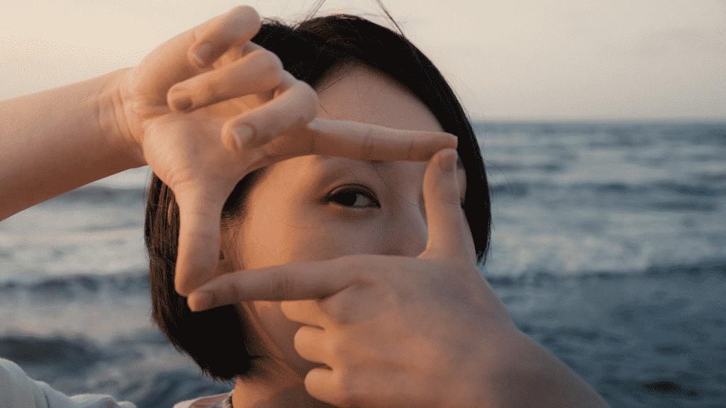 Mulher fazendo quadrado com as mãos sobre os olhos, em sinal de foco
