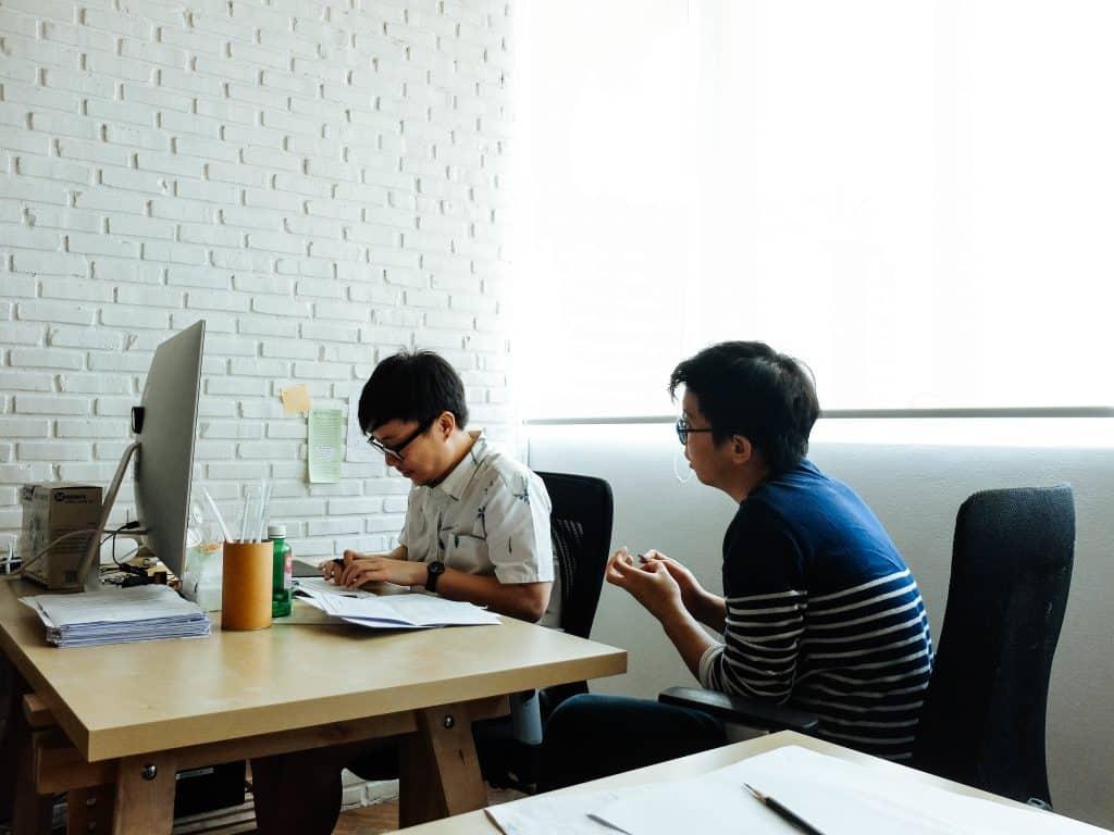 Homens asiáticos conversando num escritório.