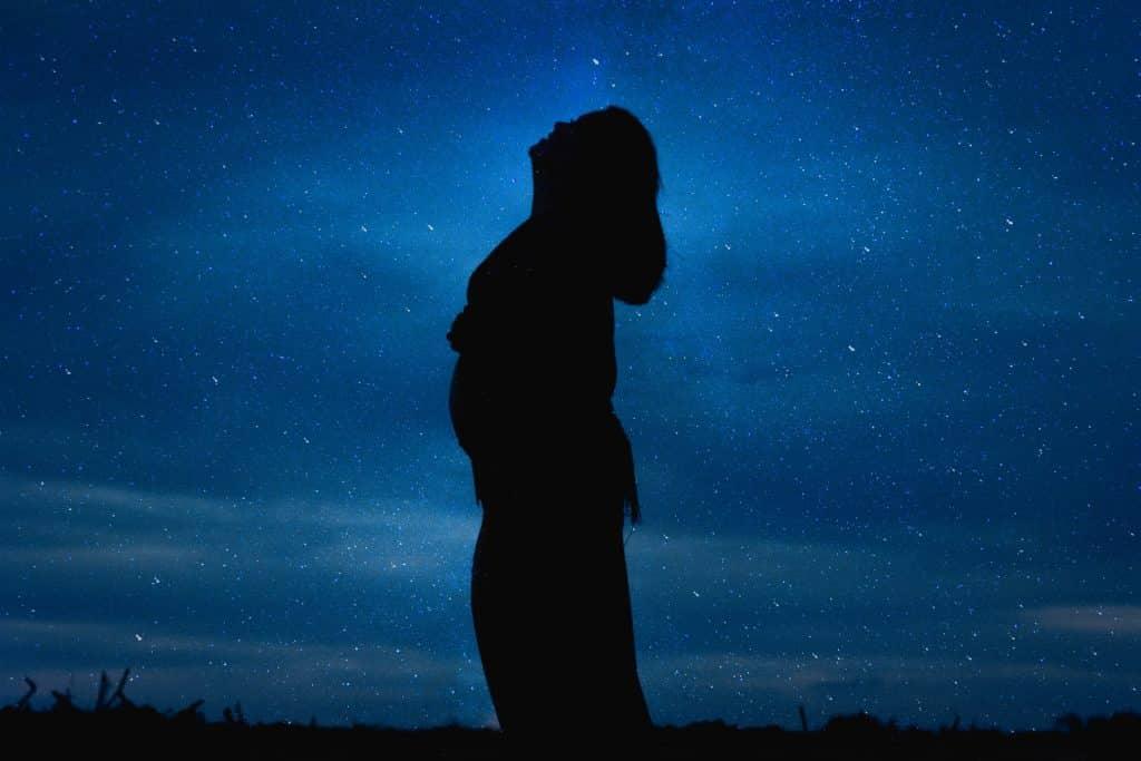 Silhueta de mulher numa noite estrelada.