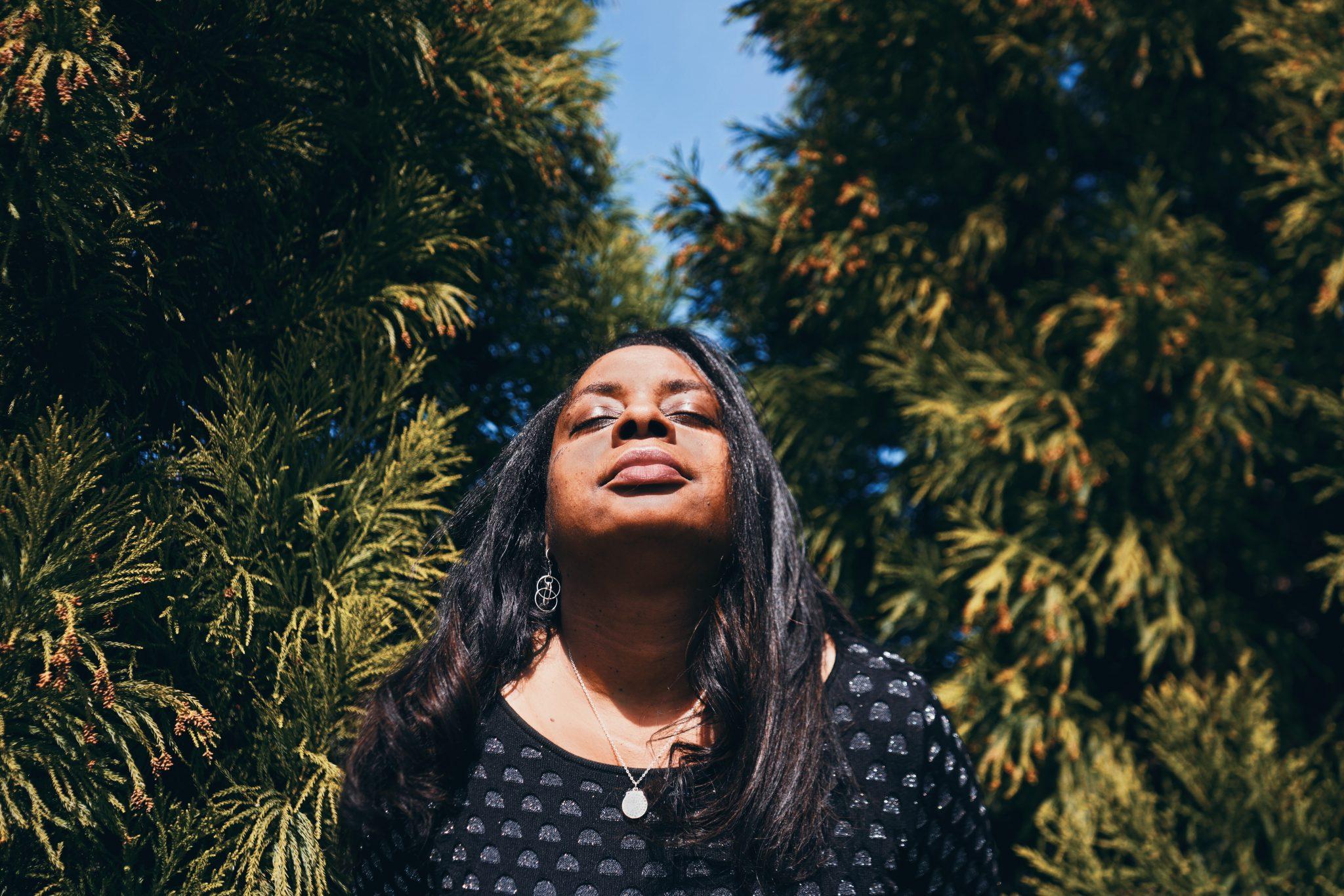 Mulher negra com os olhos fechados e cabeça levantada em meio a bosque.