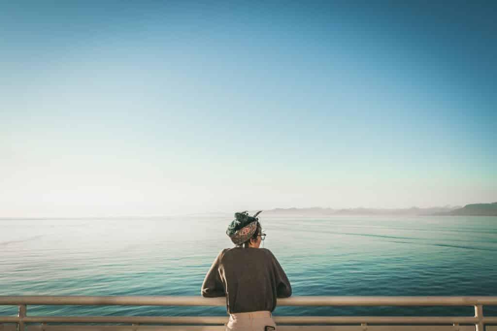 Mulher branca de costas olhando para o mar.