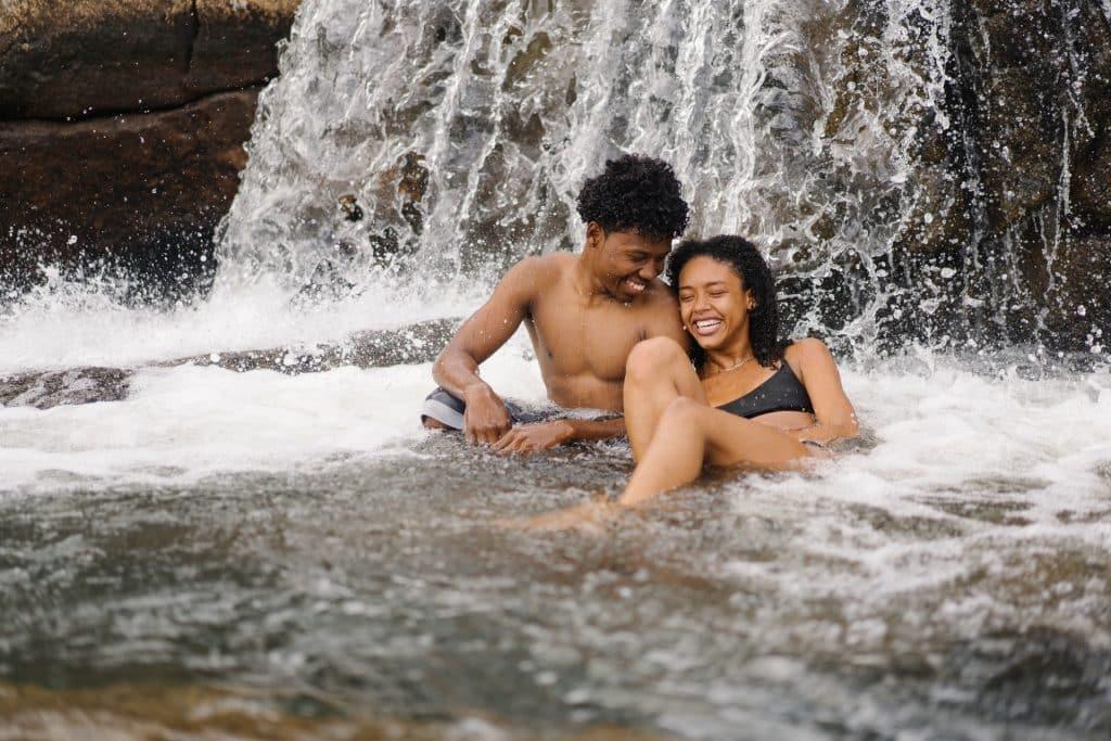 Mulher e homem negros numa cachoeira.
