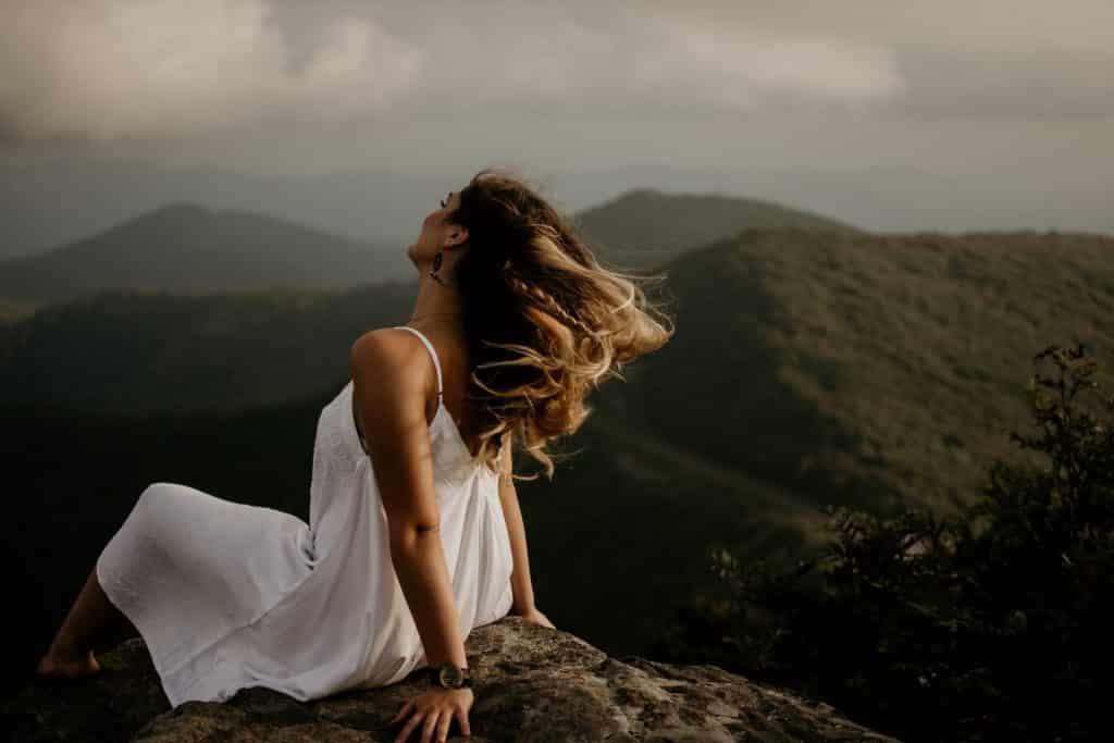 Mulher branca sentada no topo de um morro com os cabelos ao vento.