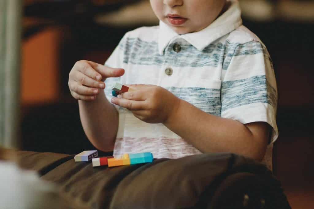 Criança branca brincando com peças coloridas.