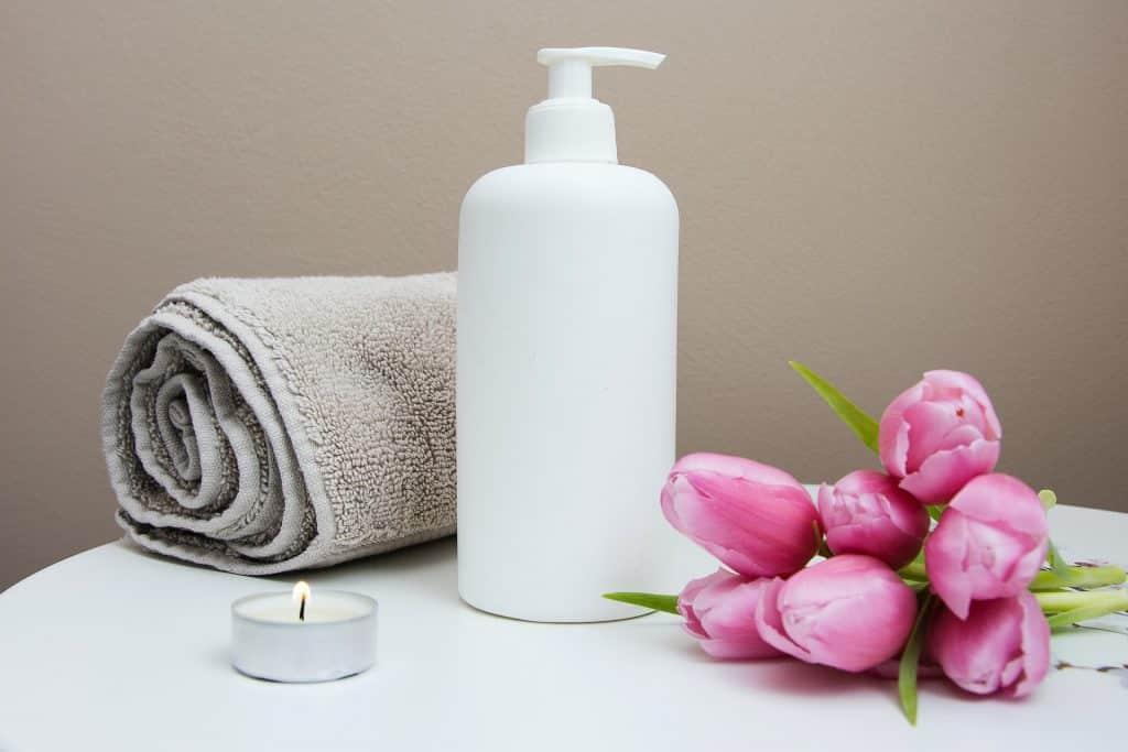 Embalagem de cosmético branco com flores rosas e toalha ao lado.