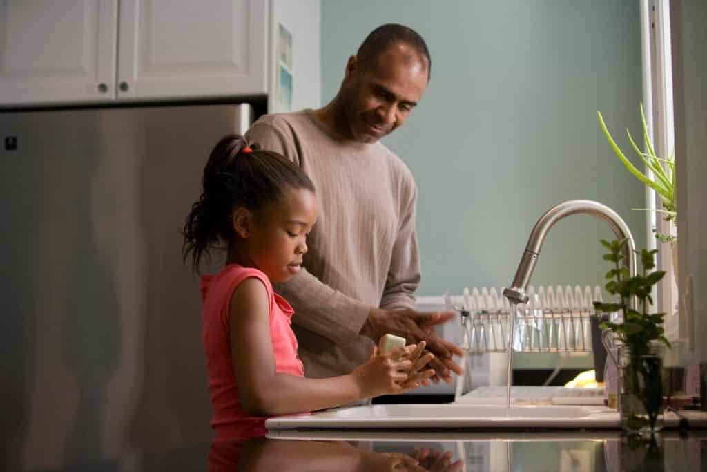 Homem e menina negros lavando as mãos.