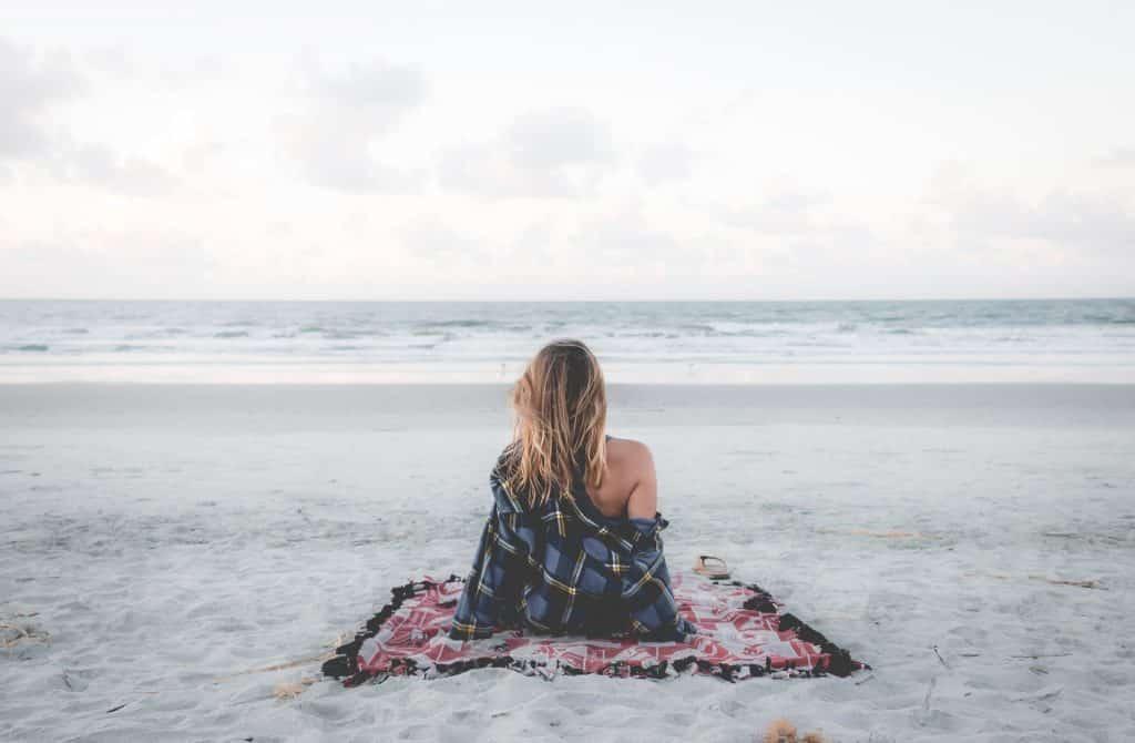 Mulher branca sentada numa praia.