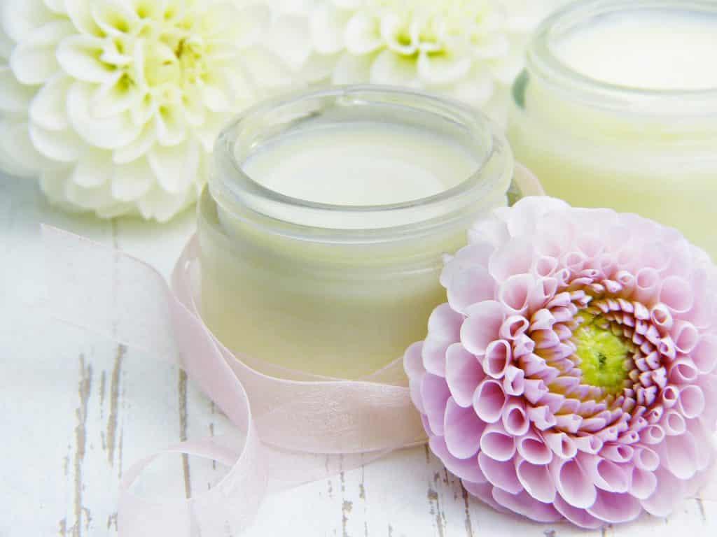 Imagem de dois potes de vidro contendo óleo de rosa-mosqueta. Um deles está decorado com uma fita rosa. Eles estão dispostos sobre uma mesa branca de madeira e ao lado flores de rosa-mosqueta na cor branca e rosa decoram todo o ambiente.