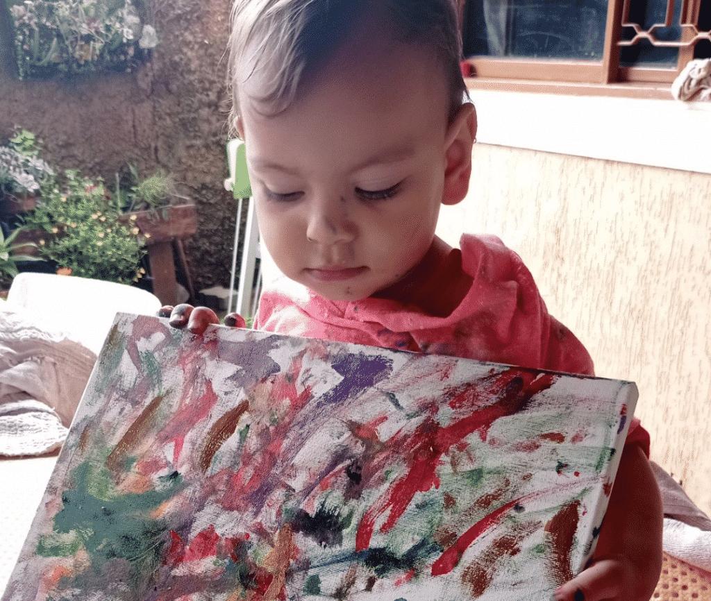 Criança segura tela pintada. Ela está em um cenário externo.