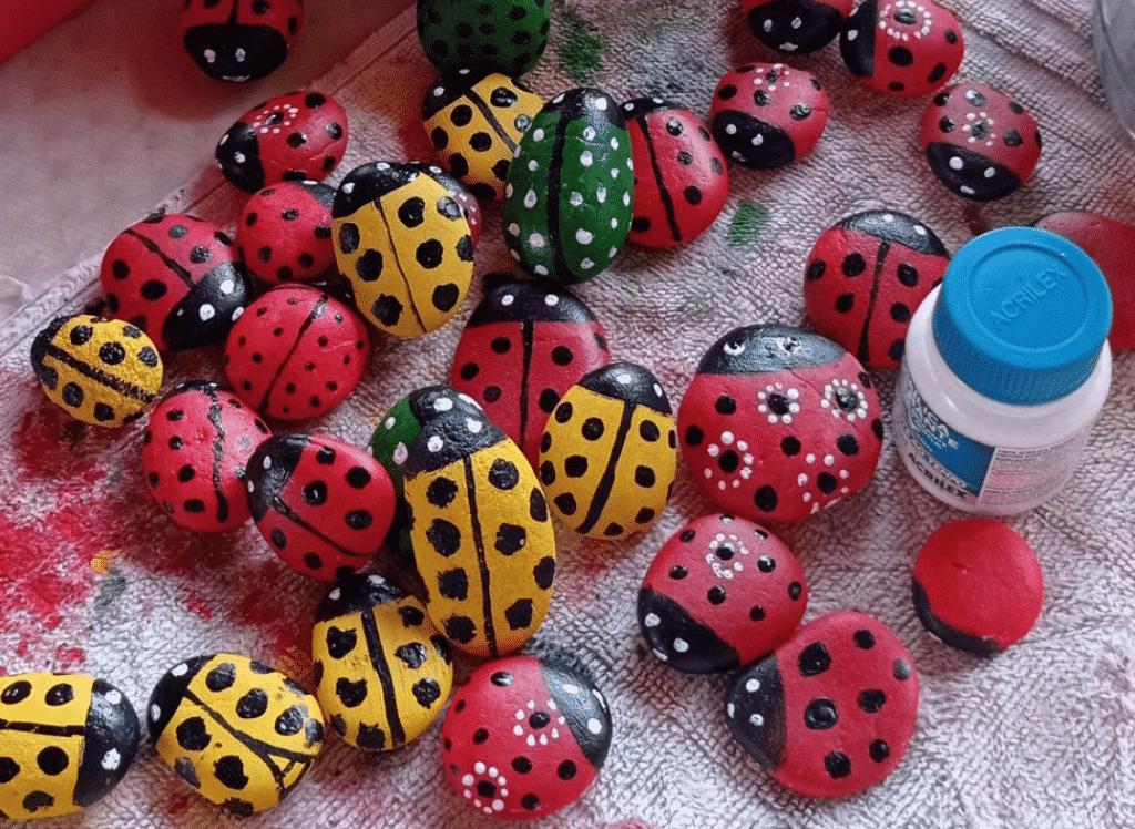 Pedras pintadas como joaninhas, elas estão sobre um tecido sujo de tinta. Ao lado delas, pote de tinta branca.