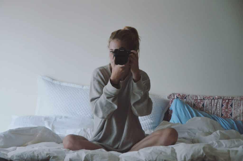 Mulher branca sentada numa cama segurando câmera fotográfica.