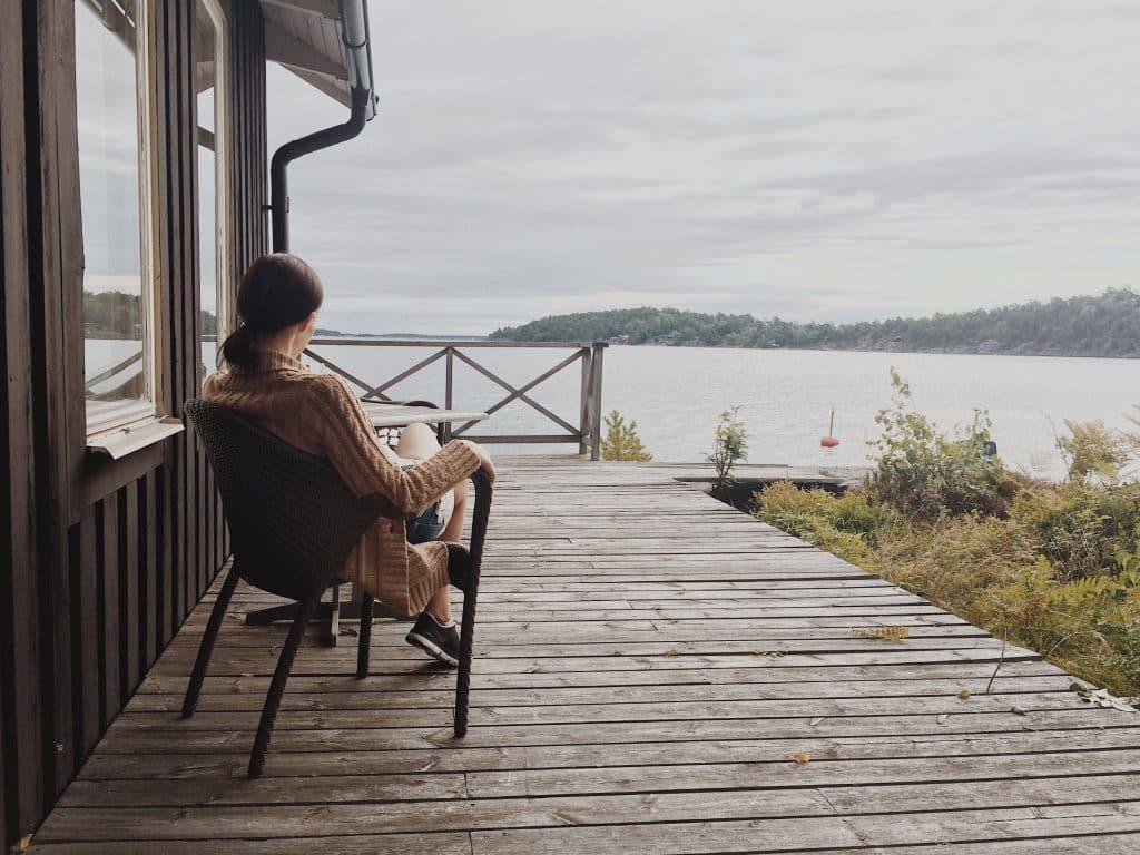 Mulher branca sentada na varanda em frente a um lago.