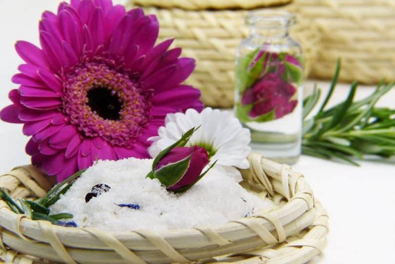 Imagem de um pequeno frasco transparente contendo óleo de rosa mosqueta. dentro dele também tem um botão de uma rosa na cor roxo. Sobre a mesa ainda temos algumas cestas de vime e uma delas está decorada com um botão de rosa e uma margarida na cor roxa.