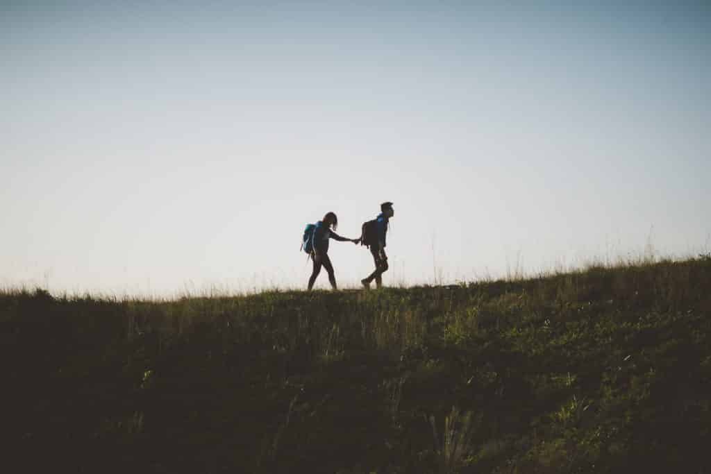 Homem e mulher andando de mãos dadas num campo.
