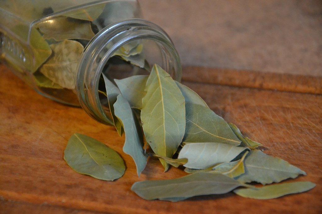 Folhas de louro caindo de recipiente de vidro sobre mesa de madeira.