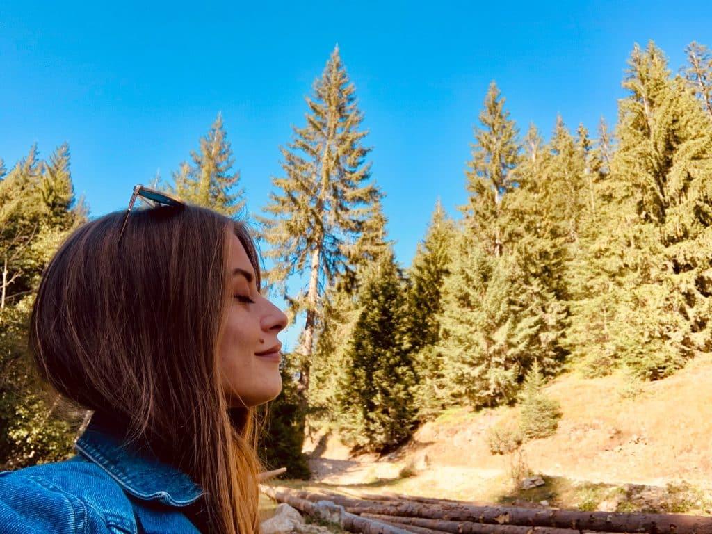 Mulher branca com os olhos fechados e expressão relaxada em meio a árvores.
