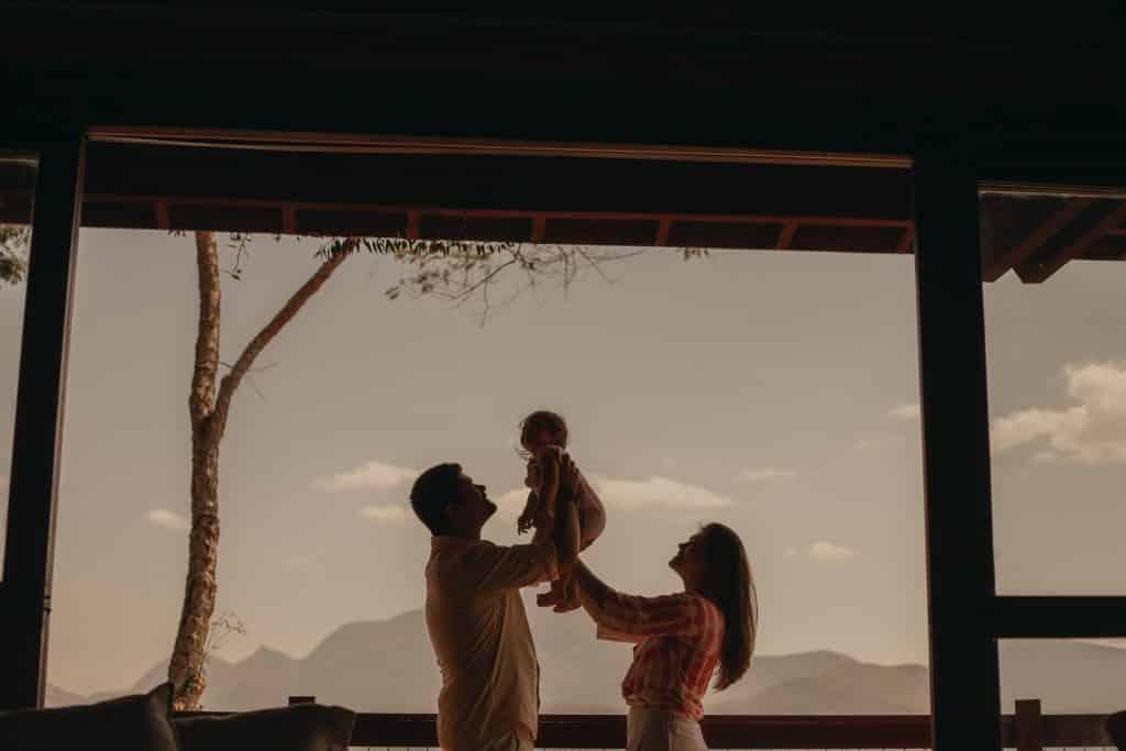 Homem e mulher segurando bebê no alto.