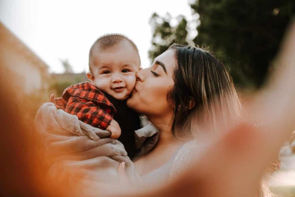Mulher branca beijando bochecha de bebê.