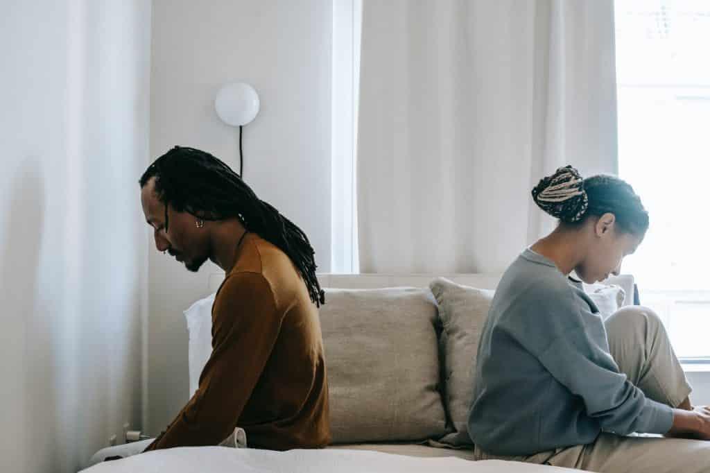 Homem e mulher negros de costas um para o outro.