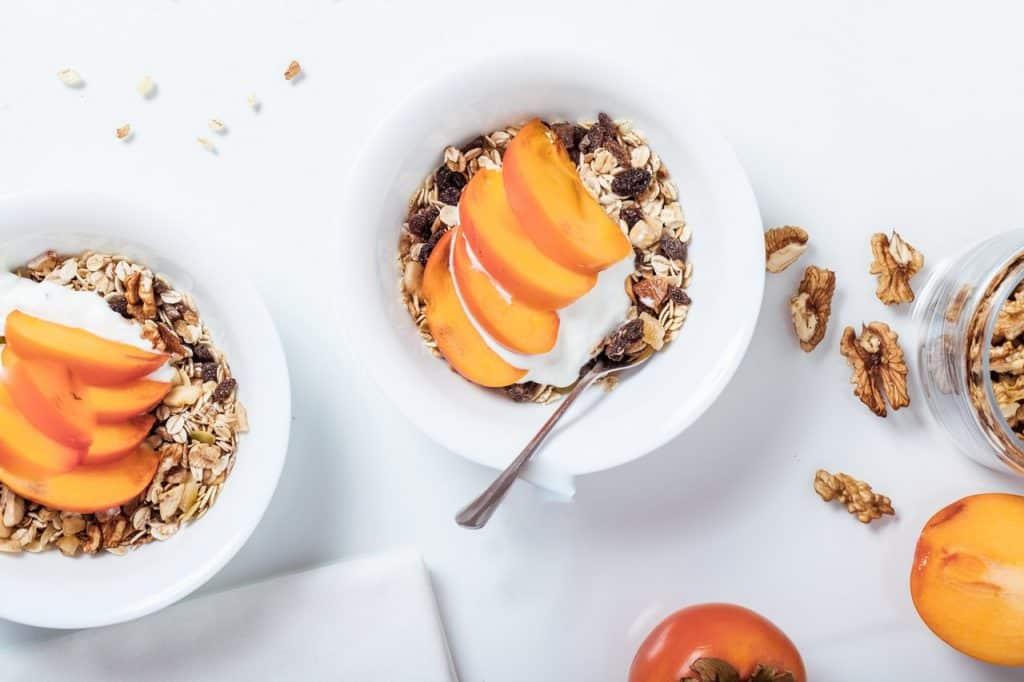 Duas tigelas brancas de cerâmica com grãos e frutas; elas estão sobre uma superfície branca.