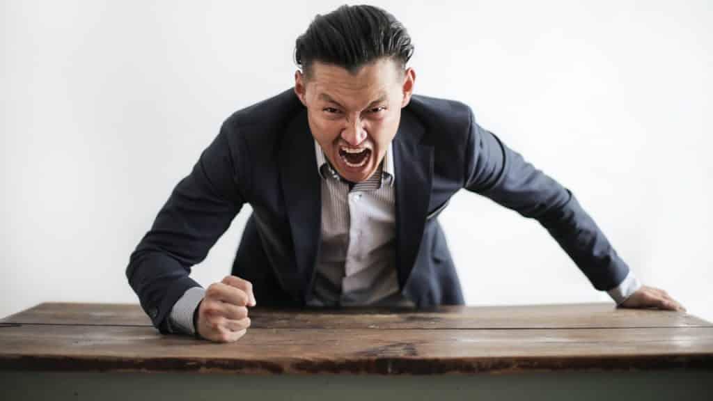 Homem gritando e com o semblante raivoso. Ele se apoia sobre uma mesa e bate uma das mãos nela.
