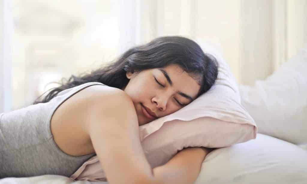 Mulher de bruços deitada em cama dorme. Seus braços estão sob o travesseiro.