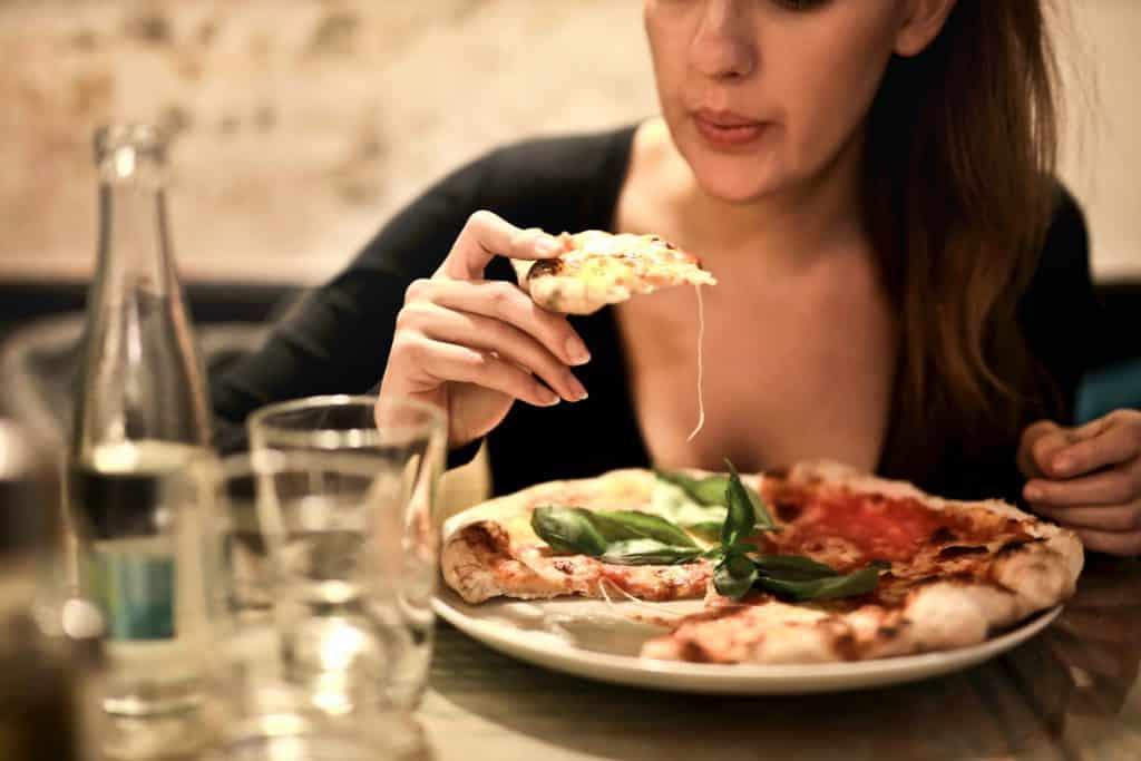 Mulher come uma fatia de pizza.