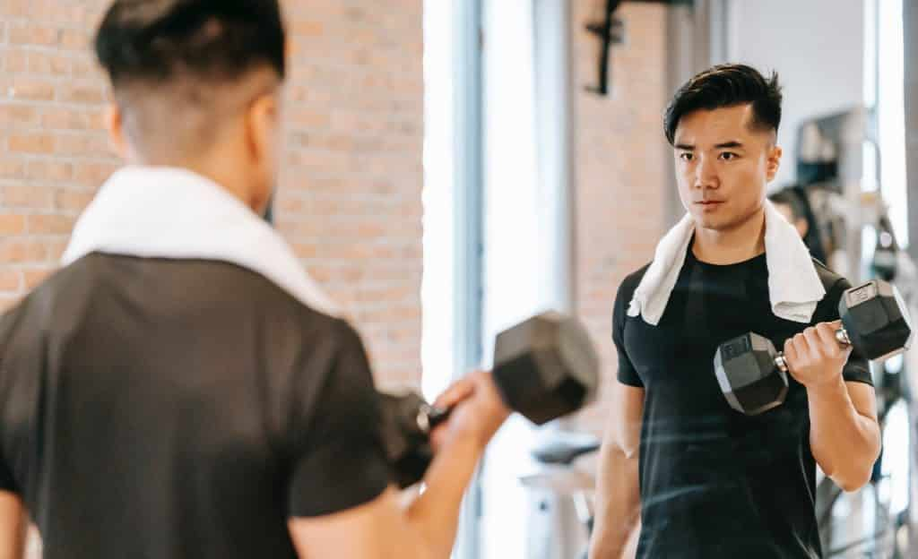 Homem olha o próprio reflexo no espelho enquanto malha um dos braços.
