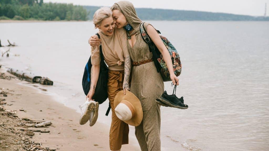 Casal anda à beira do mar em praia. Ambas sorriem e seguram os sapatos. Uma delas beija a bochecha da outra.