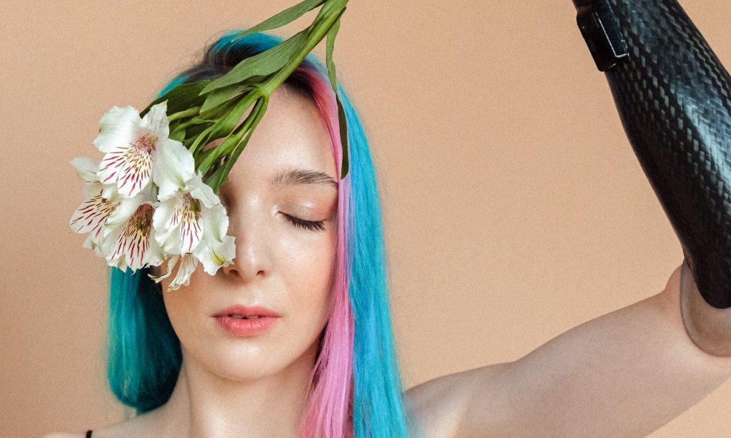 Mulher com luvas pretas segura flores sobre seu olho esquerdo; o direito está fechado.