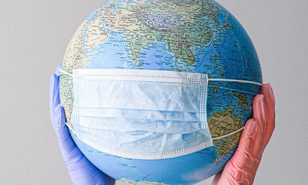 Globo terrestre segurado por duas mãos de luvas. Há uma máscara sobre o globo.