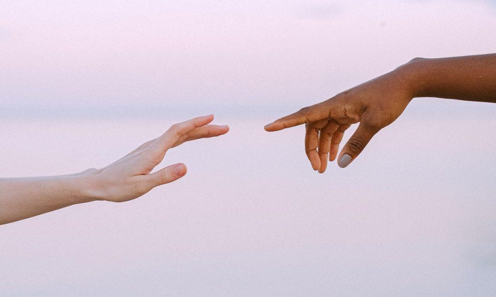 Duas mãos aproximam-se para se tocarem sobre cenário de tonalidade clara.