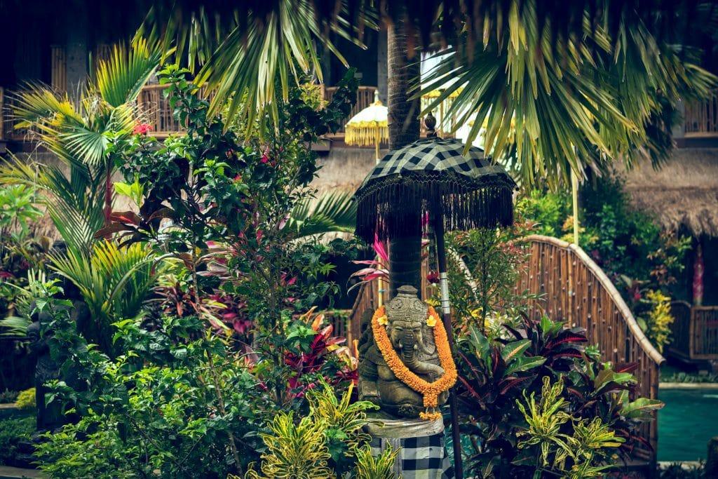 Estátua de Ganesha com colar laranja rodeada por plantas e árvores.
