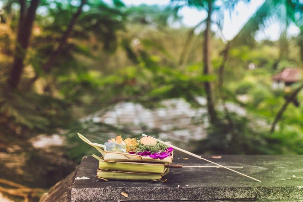 Foto de incensos queimando em um incensário de bambu em cima de uma pedra.