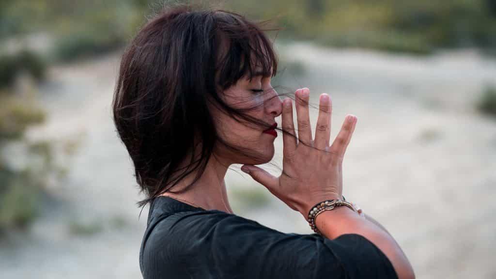 Mulher com as mãos unidas próximas do rosto.