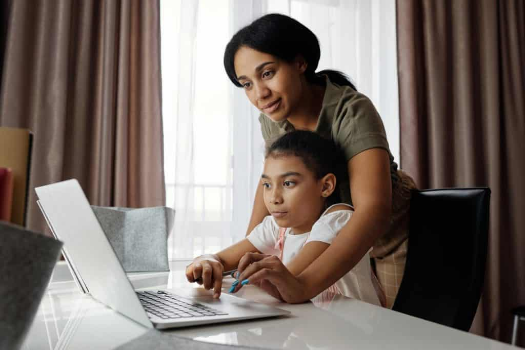 Mãe com sua filha em frente ao laptop