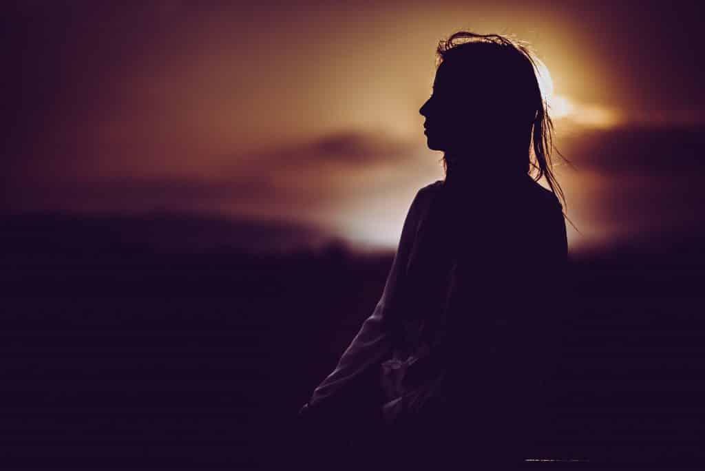 Mulher aproveitando a solitude em frente à uma paisagem de campo
