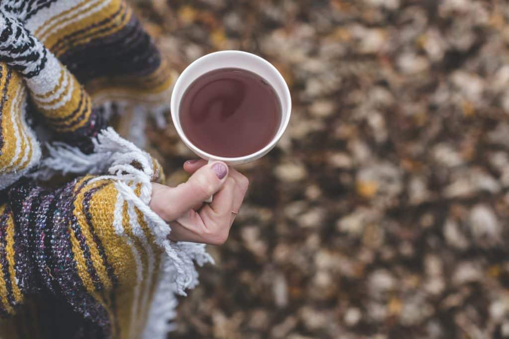 Mulher de xale segurando  uma xícara de chá