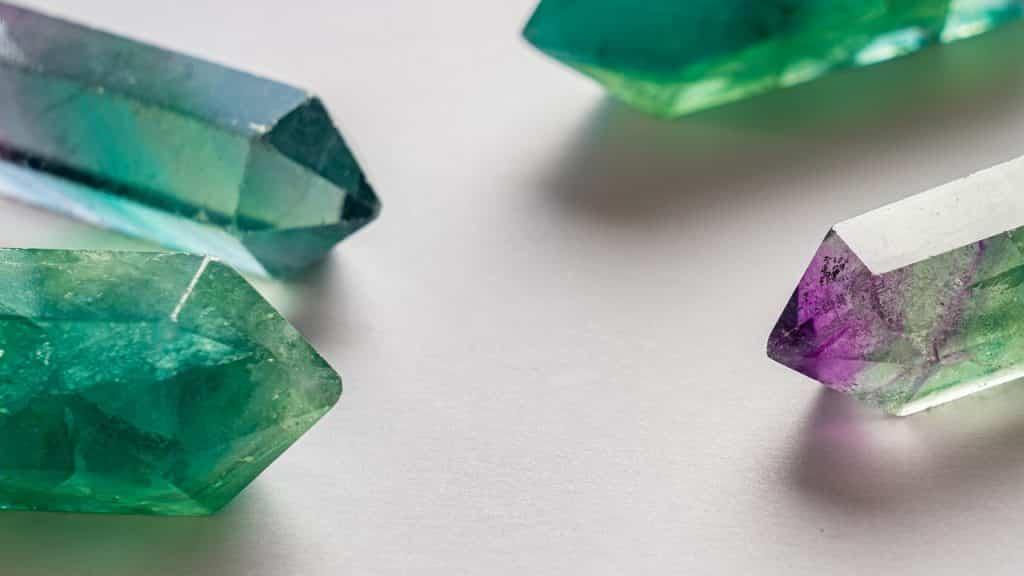 Pedras verde-esmeralda sobre superfície branca.