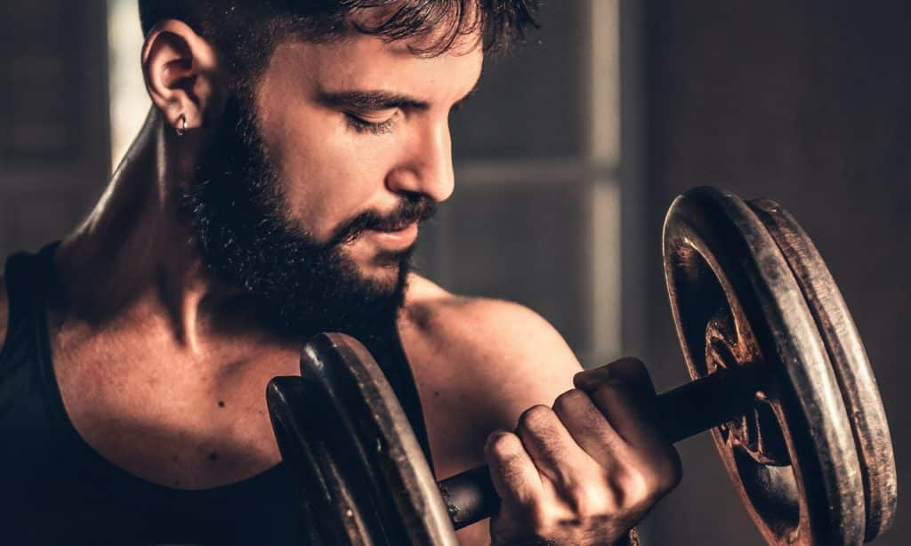 Homem levanta peso enquanto olha para o próprio braço.