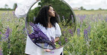 Mulher de frente ao espelho em um campo com lavandas em mãos