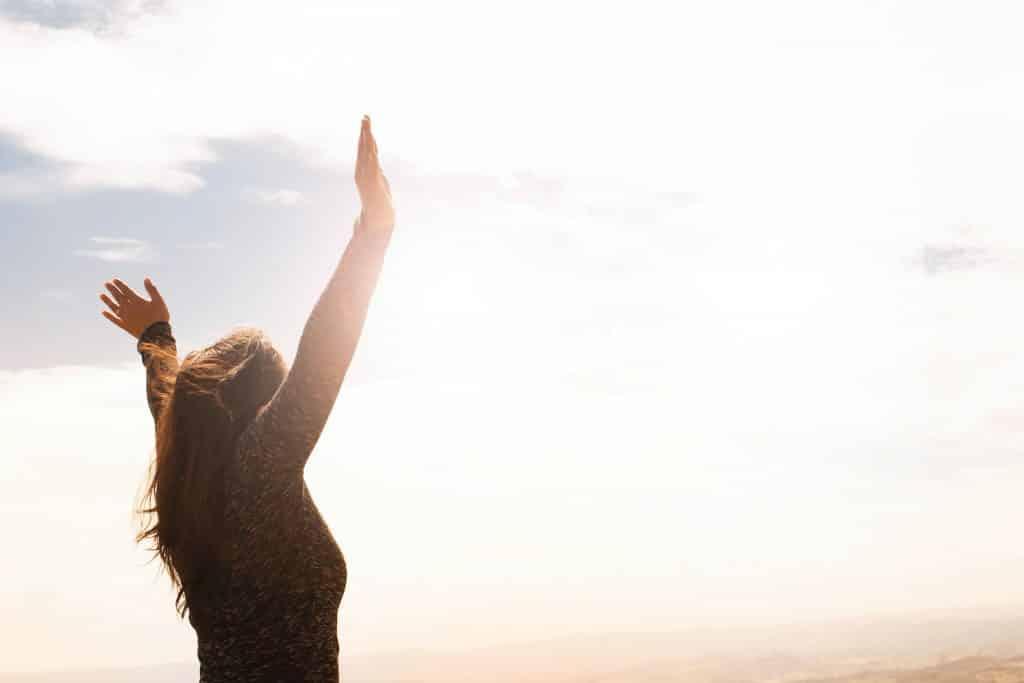 Mulher com os braços para cima e sorrindo se sentindo livre