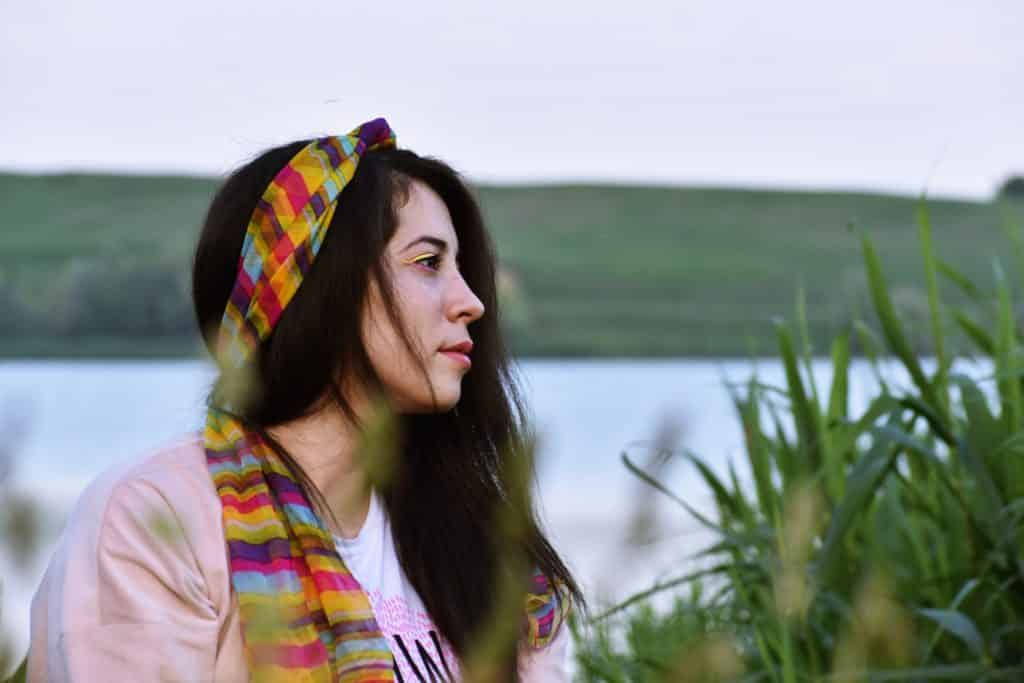 Mulher no campo pensativa enquanto olha para o horizonte