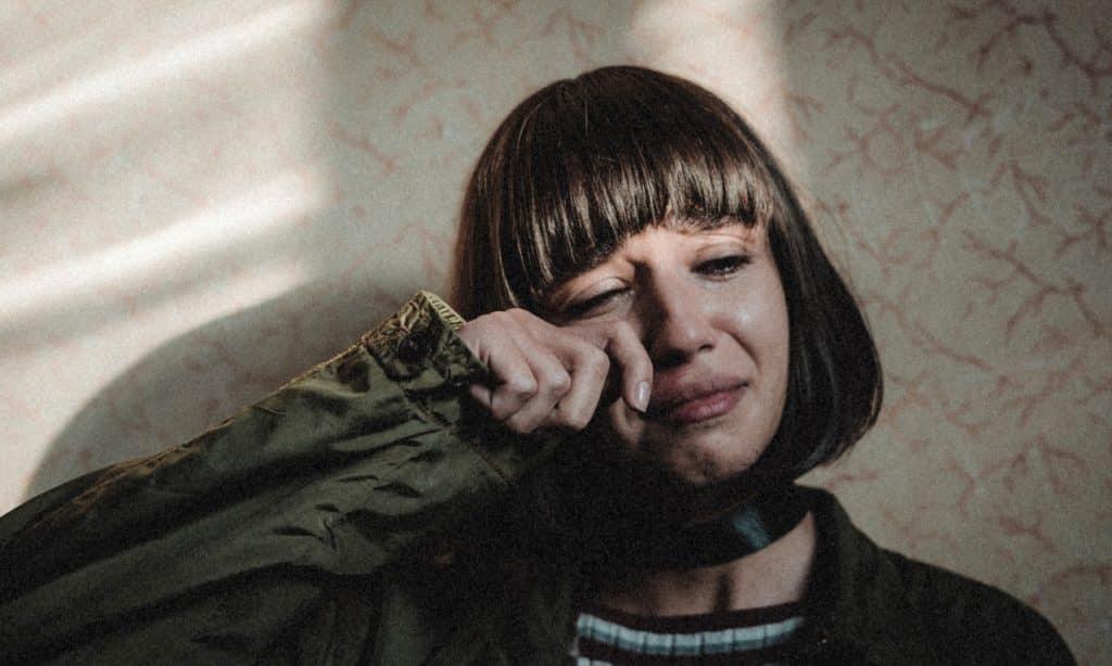 Mulher chora e enxuga as próprias lágrimas com o dedo indicador.