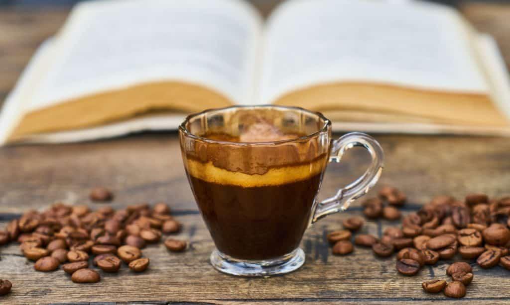 Xícara de café sobre superfície de madeira, onde também há grãos de café e um livro aberto ao fundo.