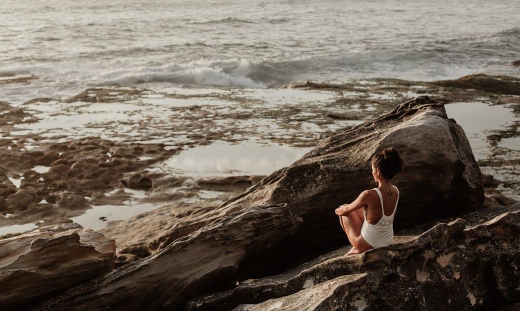 Mulher sentada em pedras à frente do mar.