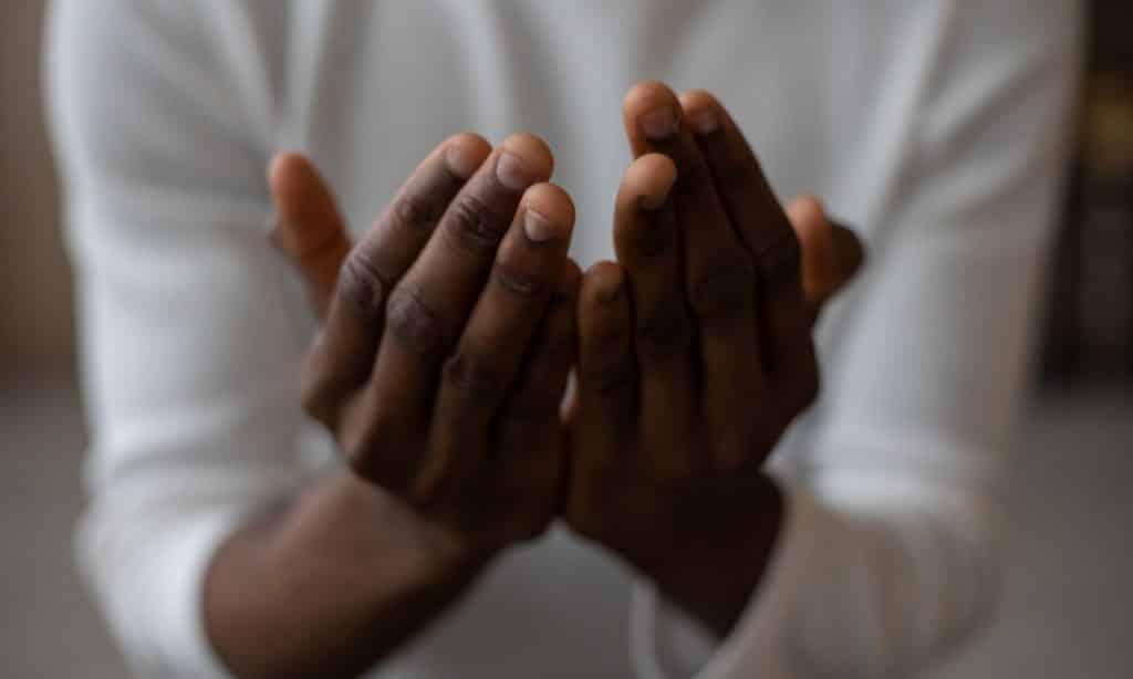 Homem faz concha com as mãos.