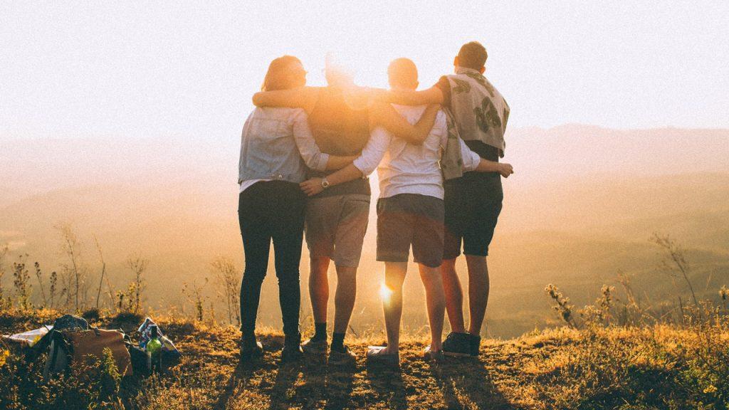 Quatro pessoas abraçadas ao pico de uma montanha.