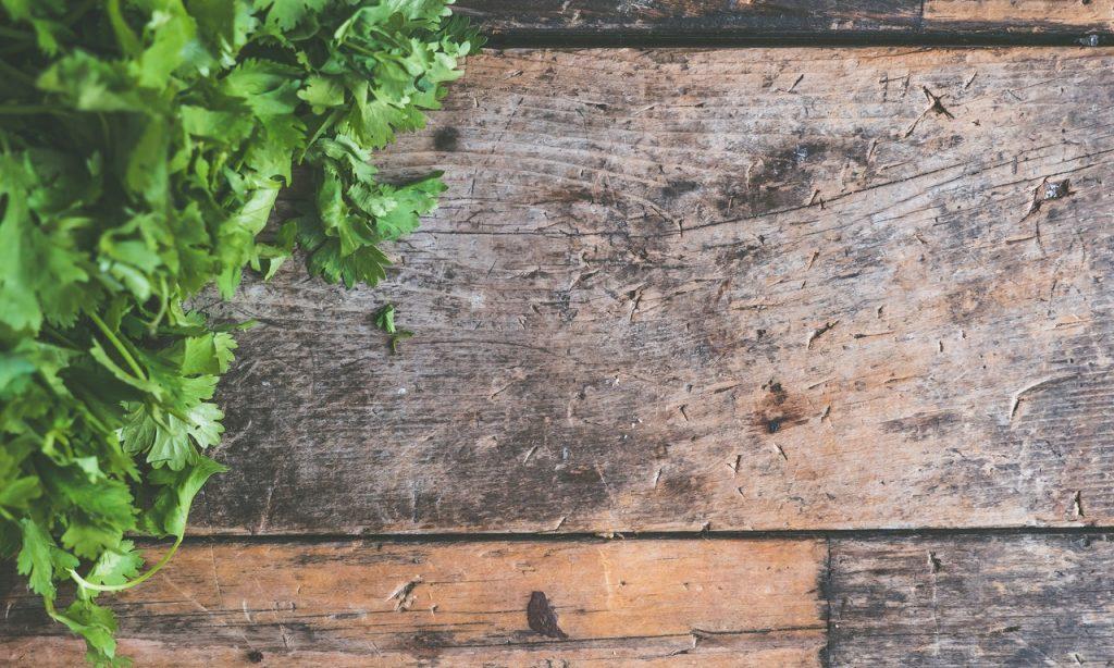 Coentro sobre superfície plana de madeira.