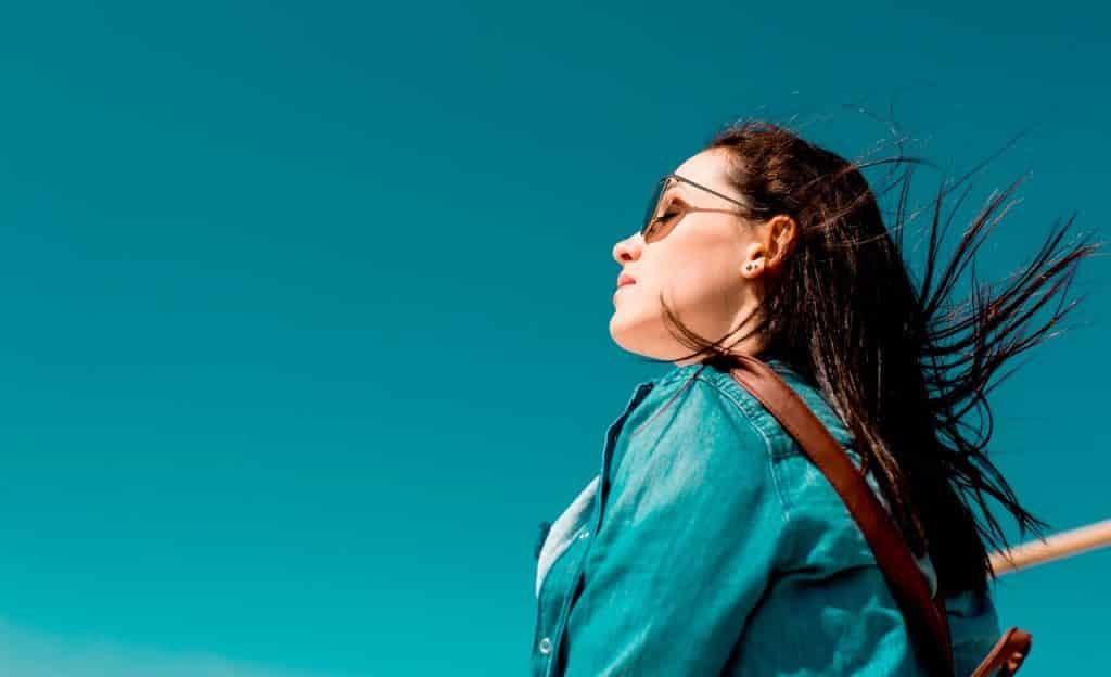 Mulher de olhos fechados e óculos escuros em ambiente externo. Ela é vista de perfil e seus cabelos voam ao vento.